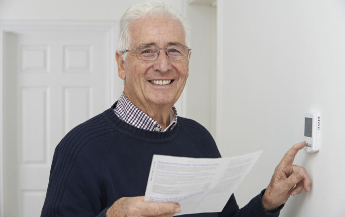Smiling Senior Man With Bill Adjusting Central Heating Thermosta